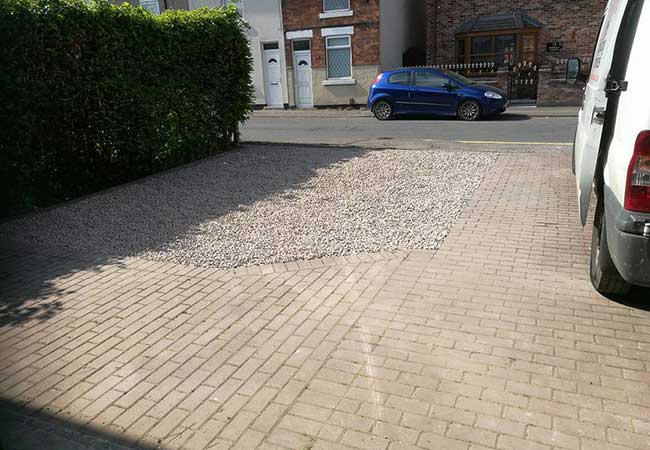 Gravel driveway infill on a once grassed area which was prepared using a compacted stone, a heavy duty weed membrane was then installed before a pink granite chipping was laid, Awsworth, Nottingham