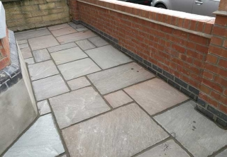 Autumn brown indian sanstone patio we layed behind a front garden wall we built at a job in West Bridgford, Nottingham