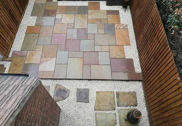A full rear landscape including fencing, brick planter, multi buff indian sandstone and stone chippings to create this patio in Awsworth, Nottingham.