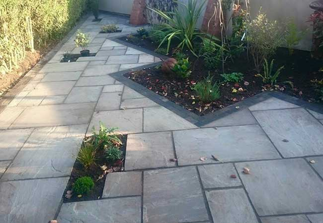 A full rear landscape project in Gedling, Nottingham, using charcoal edging sets installed with a kandla grey indian sandstone infill. Brick butresses built, coping stones on walls relayed and wall rendered.